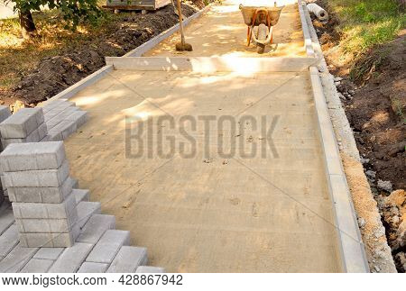 Paving Slabs Or Paving Stones Are Laid Out On The Sand Between The Curbstone. Process Of Laying Side