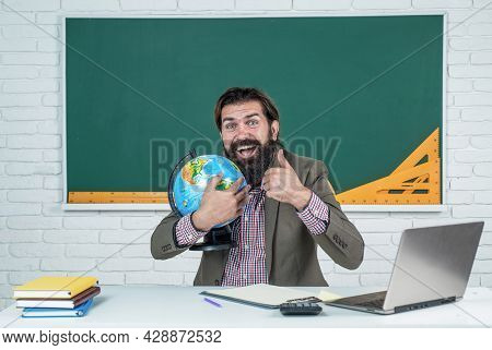 Back To School. Informal Education. Happy Mature Teacher Hold Globe And Show Thumb Up. Bearded Man G