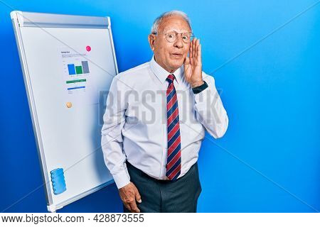 Senior man with grey hair standing by business blackboard hand on mouth telling secret rumor, whispering malicious talk conversation