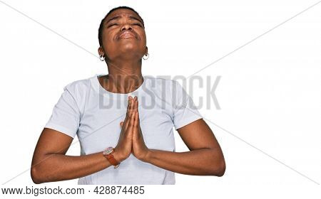 Young african american woman wearing casual white t shirt begging and praying with hands together with hope expression on face very emotional and worried. begging.