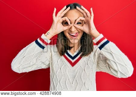Young brunette girl wearing casual student sweater doing ok gesture like binoculars sticking tongue out, eyes looking through fingers. crazy expression.