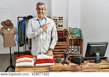 Middle age hispanic man working as manager at retail boutique pointing aside worried and nervous with forefinger, concerned and surprised expression