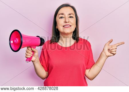 Middle age hispanic woman shouting through megaphone smiling happy pointing with hand and finger to the side