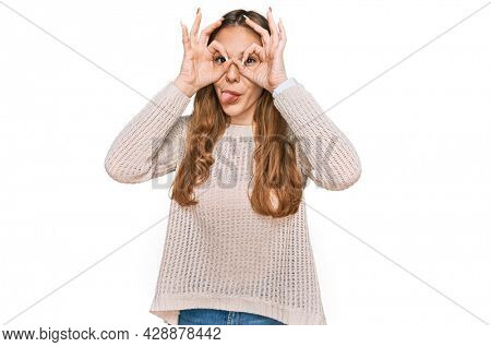 Young blonde woman wearing casual clothes doing ok gesture like binoculars sticking tongue out, eyes looking through fingers. crazy expression.