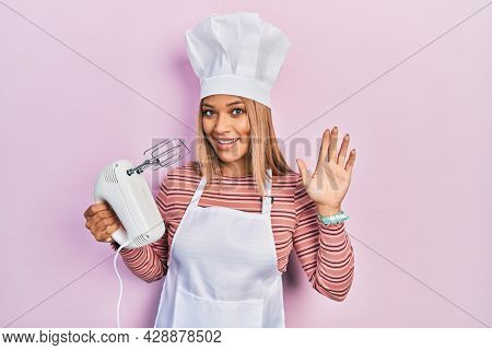 Beautiful hispanic woman holding pastry blender electric mixer waiving saying hello happy and smiling, friendly welcome gesture