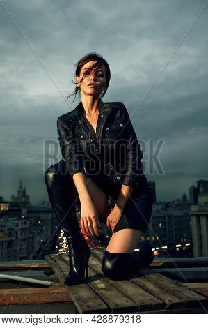Fashion Photo Of A Young Woman In A Leather Jacket, Leather Skirt And Boots, Posing On The Catwalk O