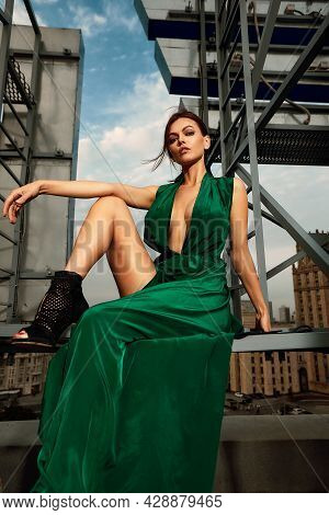 Attractive Brunette Girl In A Long Emerald Dress Posing On The Catwalk On The Roof Against The Backg