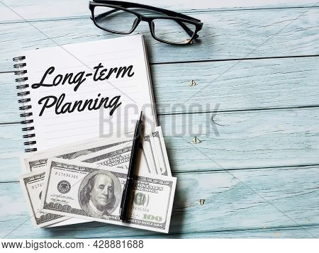 Business And Finance Concept. Phrase Long Term Planning Written On Note Book With Fake Money,pen And