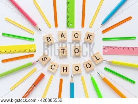 School Background With Wooden Letters Text Back To School. Flat Lay With Multicolored Supplies. Back