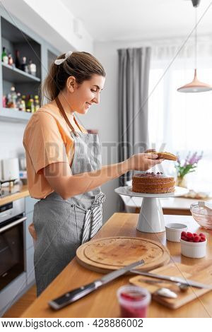 culinary, baking and cooking food concept - happy smiling young woman making layer cake on kitchen at home