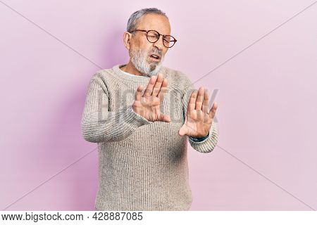 Handsome senior man with beard wearing casual sweater and glasses moving away hands palms showing refusal and denial with afraid and disgusting expression. stop and forbidden.