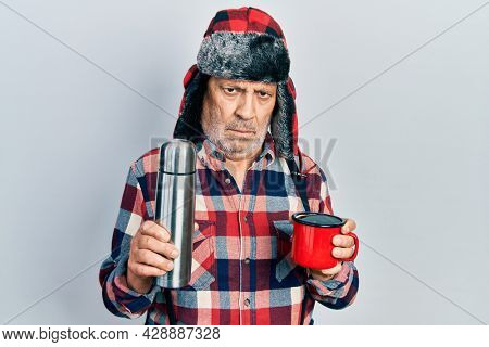 Handsome mature handyman wearing winter hat with ear flaps drinking hot coffee from thermo skeptic and nervous, frowning upset because of problem. negative person.