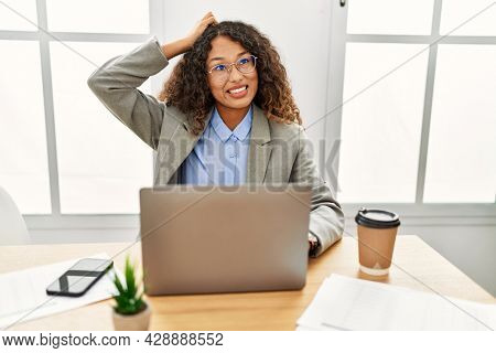 Beautiful hispanic business woman sitting on desk at office working with laptop confuse and wonder about question. uncertain with doubt, thinking with hand on head. pensive concept.