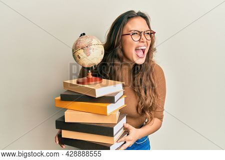 Young hispanic girl studying geography angry and mad screaming frustrated and furious, shouting with anger. rage and aggressive concept.
