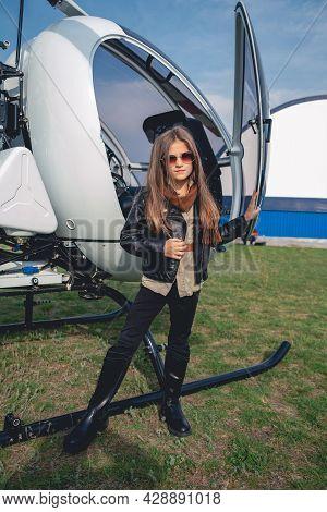 Full Length Portrait Of Tween Girl In Sunglasses Near Open Helicopter