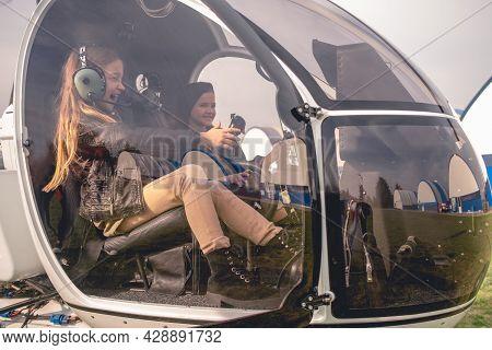 Excited Tween Girl In Aviator Headphones Sitting In Helicopter Cockpit