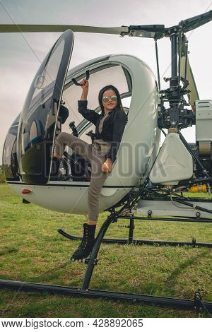 Smiling Tween Girl In Mirrored Sunglasses Standing On Footboard Of Helicopter