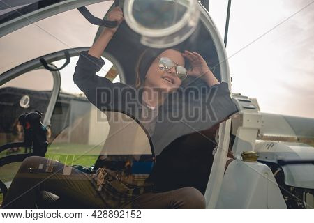 View Through Glass Of Helicopter Cockpit Of Cheerful Tween Girl Looking At Sky
