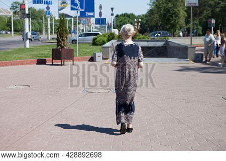 A Thin, Lonely, Old Pensioner Woman Walks Down The Street. Back View. 06.19.2021. Minsk, Belarus.