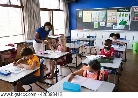 African american female teacher spraying hand sanitizer on hands of girl at elementary school. education back to school health safety during covid19 coronavirus pandemic