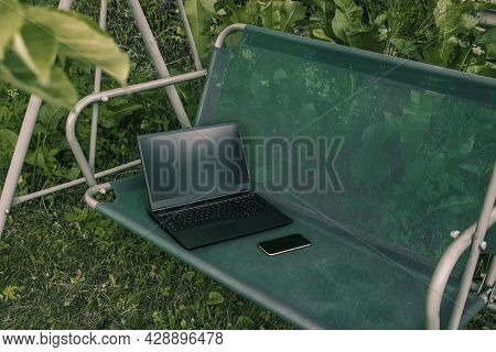 Remote Work Or Education. A Workplace In The Fresh Air.  A Laptop, A Smartphone, A Notebook On A Swi