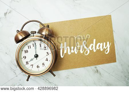 Hello Thursday Typography Text On Paper Card With Alarm Clock On Marble Background