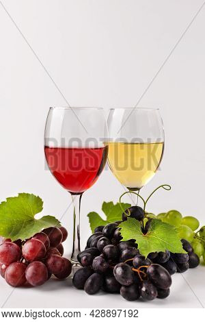 Wine Composition With Wine Glasses And Grape. Glasses Of Red And White Wine And Variety Of Grape On