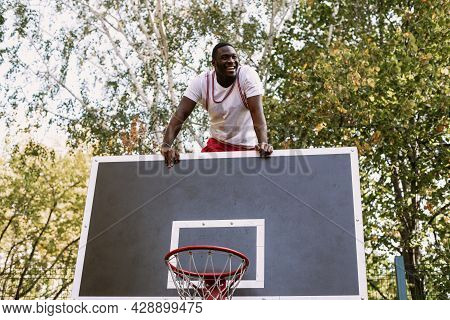 Portrait Of A Handsome Black Young Man Holding A Basketball On A Basketball Court. Take A Break Duri