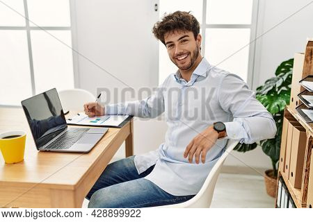 Young hispanic businessman smiling happy working at the office.