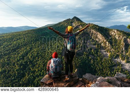 Two Happy Hikers With Backpacks Are Standing With Raised Arms And Looking At Mountains And Sunset. T