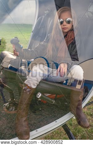 Preteen Girl On Pilot Seat Holding Control Handle Behind Glass Of Helicopter Cockpit