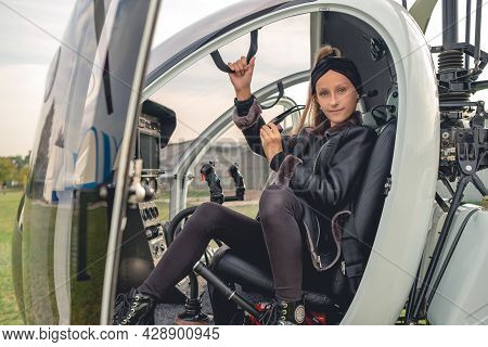 Tween Girl With Sunglasses In Hand Sitting On Pilot Seat In Helicopter