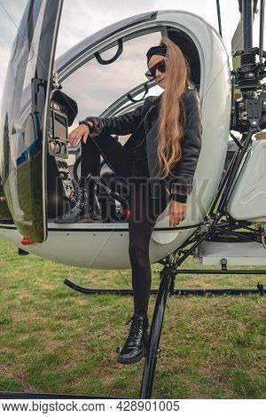 Confident Tween Girl In Black Standing On Footboard Of Helicopter