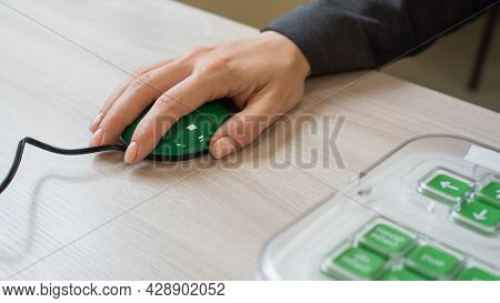 A Woman With Cerebral Palsy Uses A Specialized Orgonomic Computer Mouse.