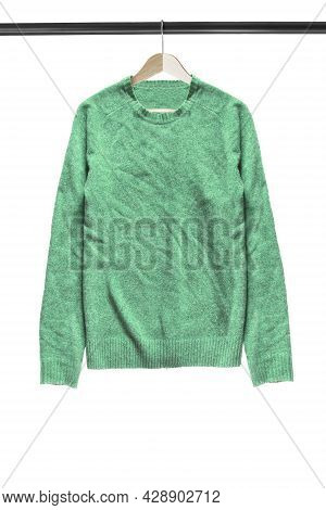 Green Wool Pullover Hanging On Wooden Clothes Rack Isolated Over White