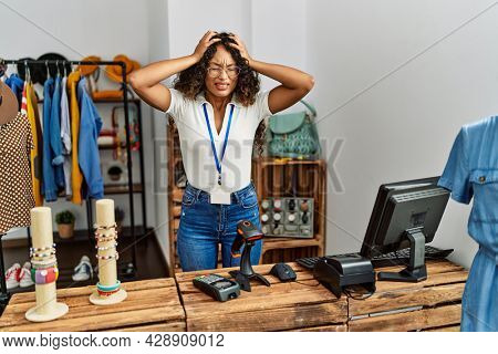 Beautiful hispanic woman working at clothing shop suffering from headache desperate and stressed because pain and migraine. hands on head.
