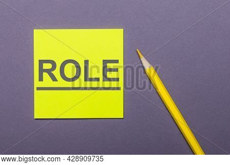 On A Gray Background, A Bright Yellow Pencil And A Yellow Sticker With The Word Role