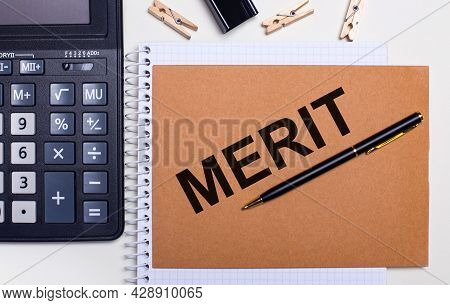 On The Desktop Is A Calculator, A Pen And Clothespins Near A Notebook With The Text Merit. Business