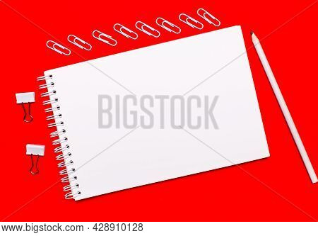 On A Bright Red Background, A White Pencil, White Paper Clips, White Paper Clips, And A White Blank
