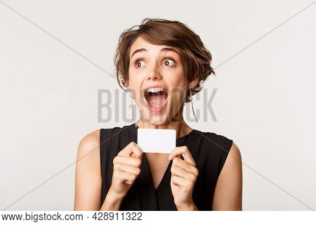 Close-up Of Excited Young Pretty Woman, Looking Left Ecstatic, Showing Credit Card, Standing Over Wh