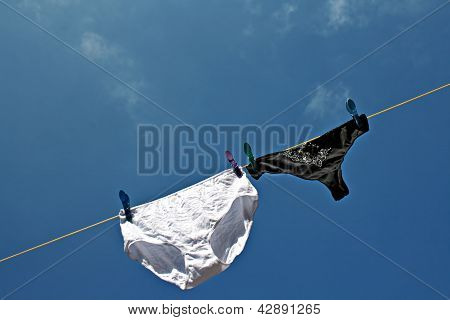 Panties hanging on washing line to dry one large one small. poster