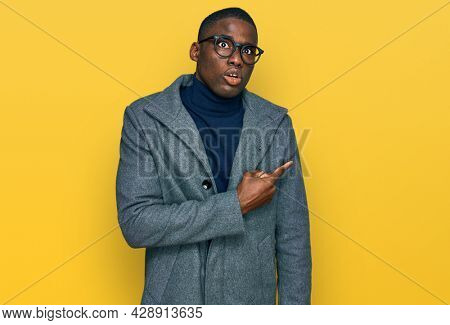 Young african american man wearing business clothes and glasses pointing aside worried and nervous with forefinger, concerned and surprised expression