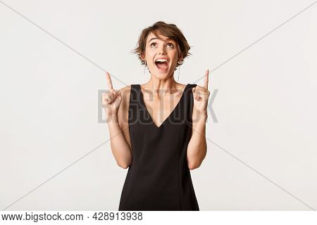 Excited Attractive Woman Looking And Pointing Up With Amazed Ecstatic Expression, Standing Over Whit