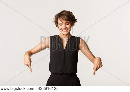 Happy Adult Woman In Black Dungarees Pointing Fingers Down, Looking Downwards With Pleased Smile