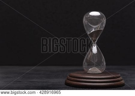 Hourglass On Black Background. Urgency And Outcome Of Time. Time Management