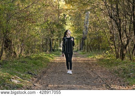 Beautiful Girl Walks In The Autumn Park. Young Beautiful Woman In Black Clothes In The Forest. Alley