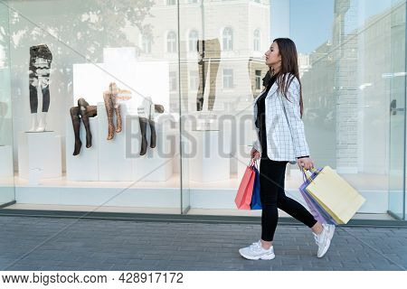 Young Woman With Colorful Packets Walks Past Shop Windows. Shopaholic.