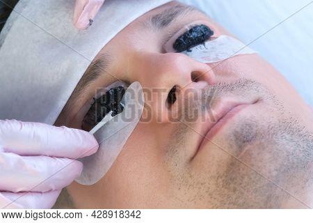 Beautician Wiping Black Paint From Mans Eyelashes On Laminating Lash Procedure.