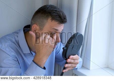 Man Looking At Mirror On His Lashes After Eyelash Laminating Lifting Procedure.