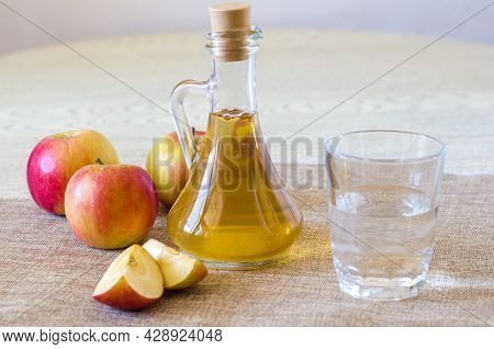 Apple Cider Vinegar In A Glass Bottle On A Light Background With A Glass Of Water. Malic Acid Is Ben